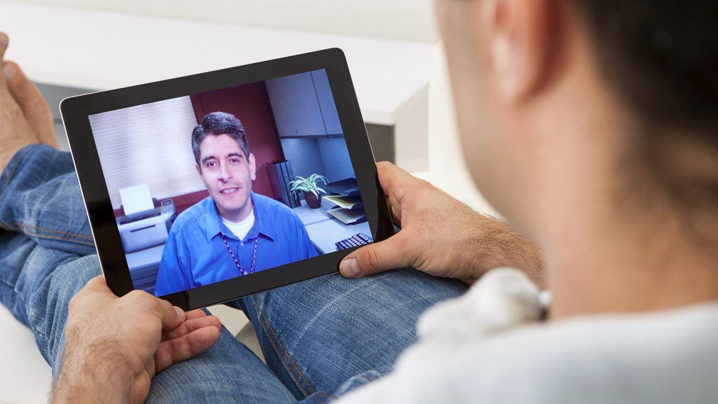 Individual using a tablet to talk to their physician from home